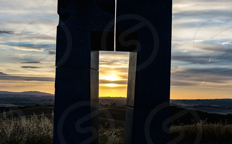 The setting sun at the center of a monument in the Crete Senesi photo