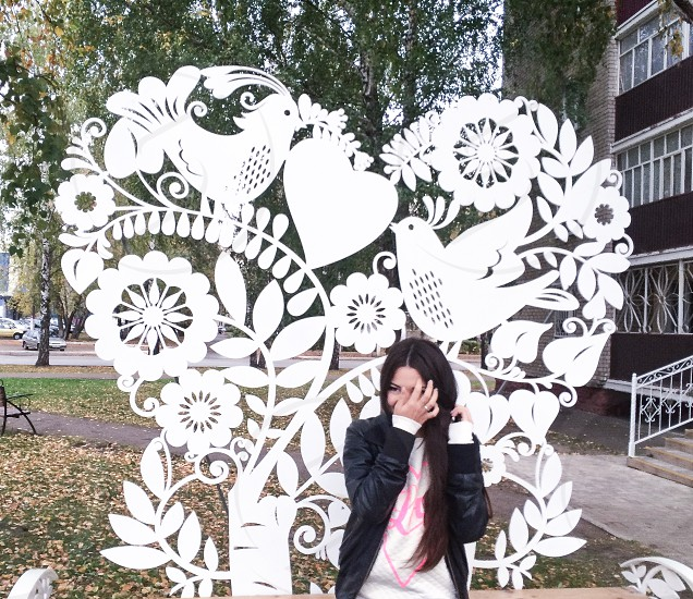 woman in black zip up jacket fixing hair in front of white birds floral heart fence near trees during daytime photo