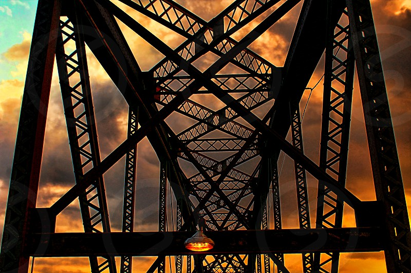 The upper beams of an old bridge are silhouetted against the bright sky of an orange sunset. photo