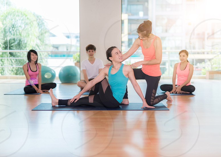 fitness sport training gym and lifestyle concept - group of smiling women with trainer stretching on mats in the gym photo
