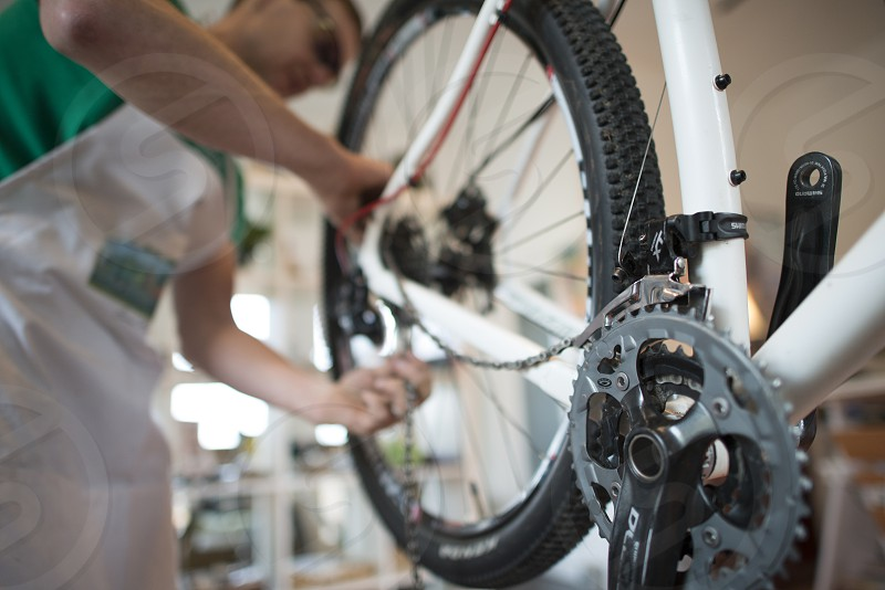 man in green t-shirt with white apron fixing white bicycle photo