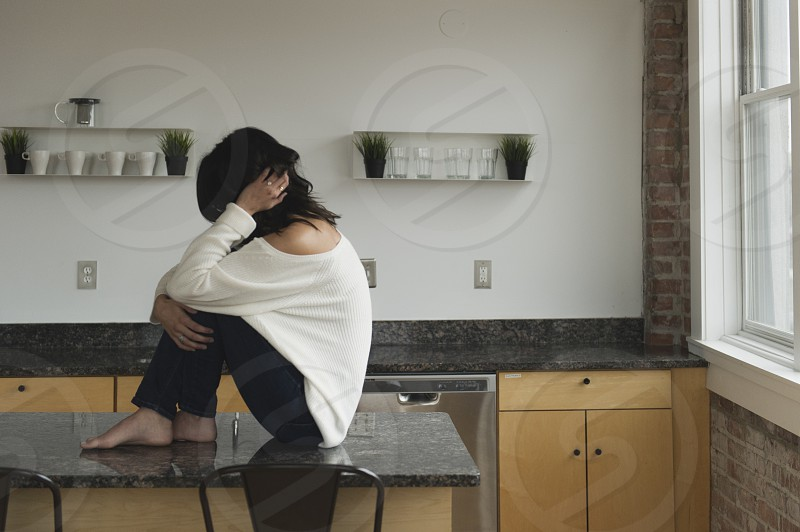 Young brunette woman sitting on kitchen counter photo