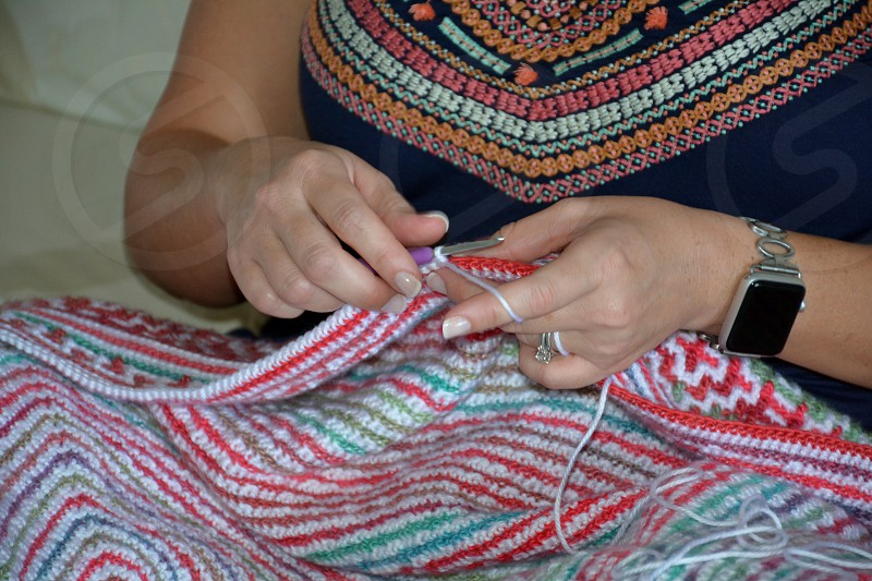 female hands crocheting a multicolered blanket photo