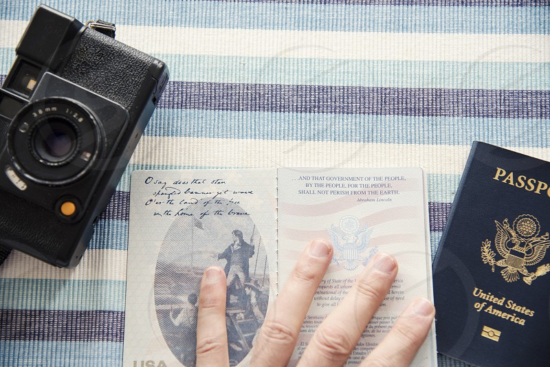 Overhead view of hand holding passport open with camera on table top. photo