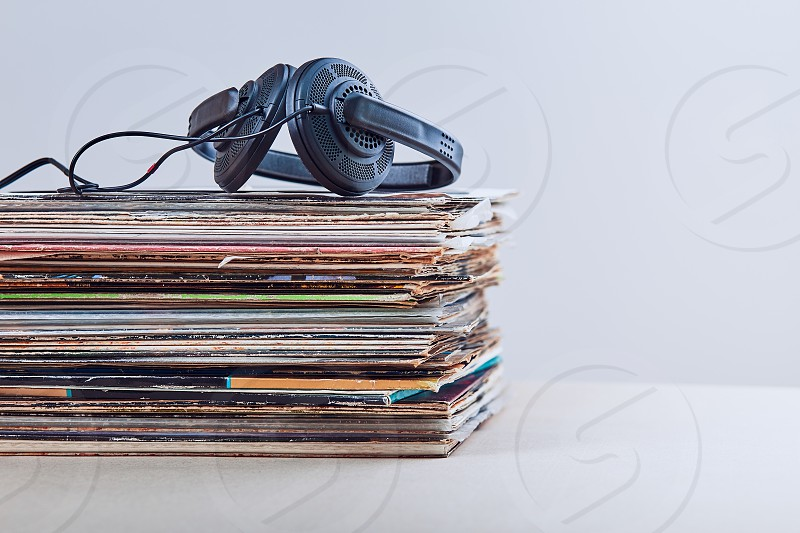 Stack of many black vinyl records headphones put on the top of vinyls. Copy space for text. Candid people real moments authentic situations photo