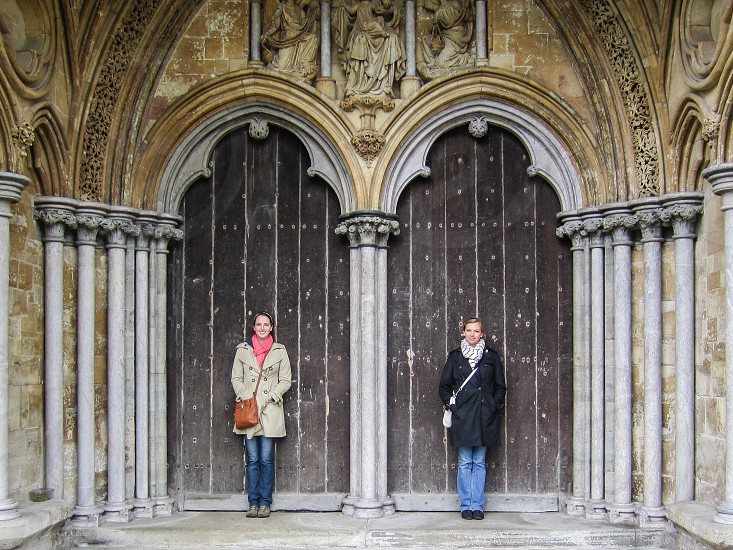 Two young travelers in front of the doors of an English cathedral. photo