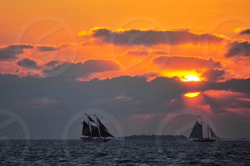 sailboats on body of water during orange sunset behind dark clouds photo