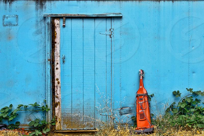 Old orange vacuum leans against a blue shed photo