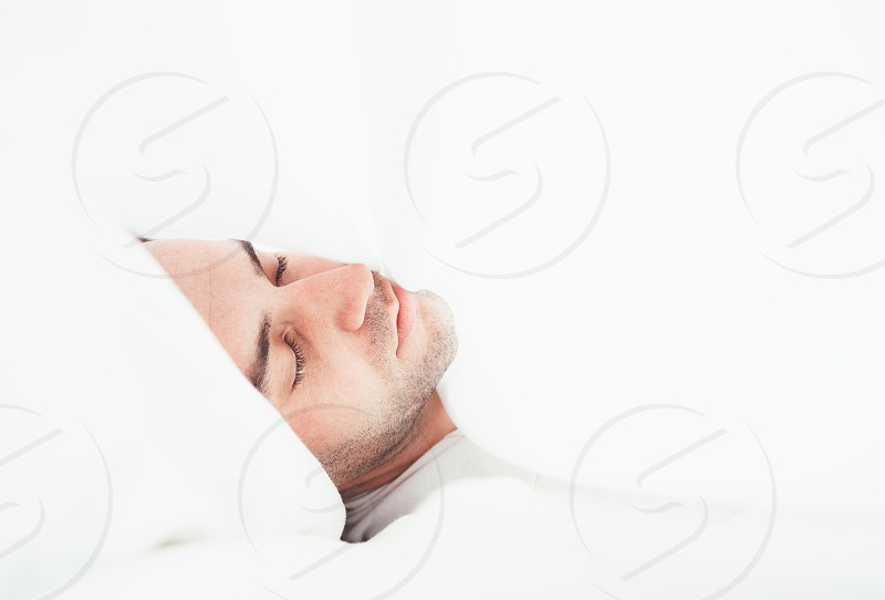 Young man lying in the sheets photo