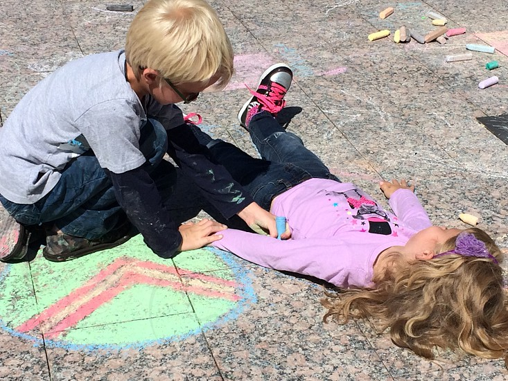 boy tracing girl's body on concrete floor photo
