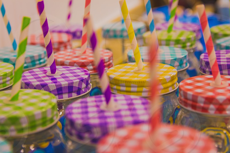 Many jars with colorful lids and drinking straws. photo