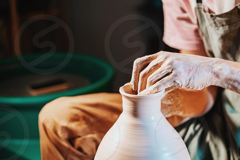 Overhead view of man making jug on pottery wheel. Potter shapes the clay product - jug - with professional tools top view. Small business owner working in workshop photo