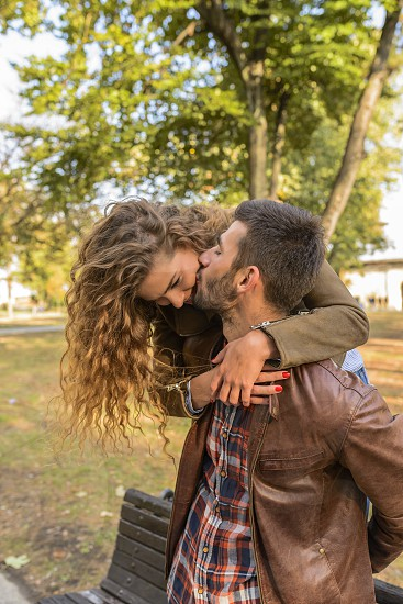 Attractive long haired girl is hugging his boyfriend while he is kissing her in the public park photo