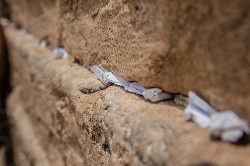Notes to God in the cracks between the bricks of the Western Wall in the old city of Jerusalem Israel. photo