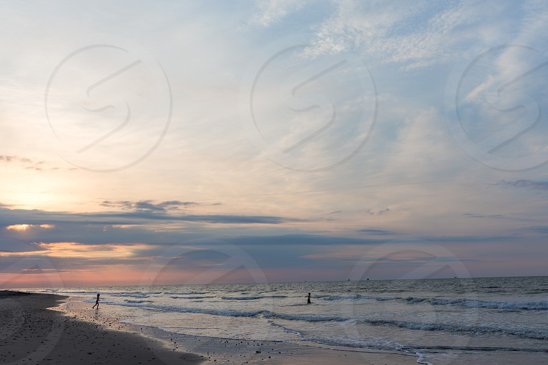 Children playing in the waves along Folly Beach at sunrise.  South Carolina. photo