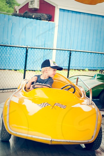 boy summer carnival fair amusement park park rides ride riding car driving yellow race car circles around carousel fun happy cap hat blue red flags checkerboard hood joy photo