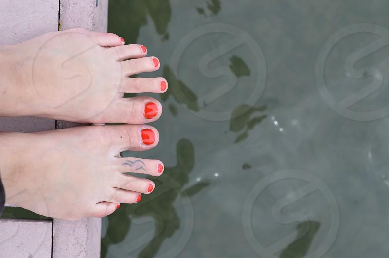 Dock feet water orange toenail polish tattoo balance  photo
