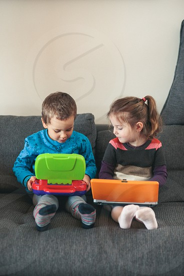 Two children playing with laptops learning basic digits characters sounds and images. Little girl and boy sitting on sofa and playing together at home. Candid people real moments authentic situations photo
