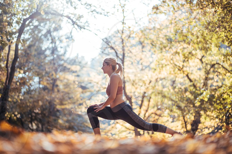Young sporty woman stretching after workout in the park in autumn photo