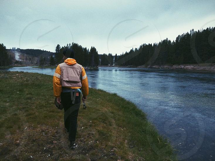 man in orange jacket walking along a river bank photo