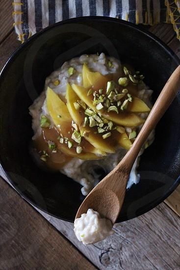 Coconut milk rice pudding with fresh mangoes coconut dulce de leche and pistachios. photo