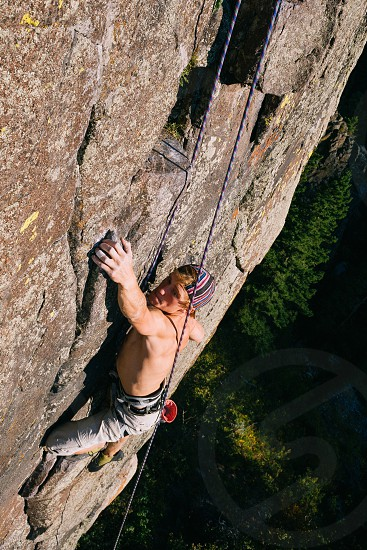 A climber reaches for a good hold on a granite wall in Bozeman MT photo