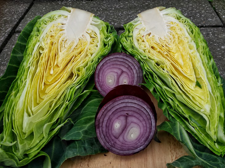 Cabbage and red onion cut into halves on a wooden board with stone flagged background.. photo
