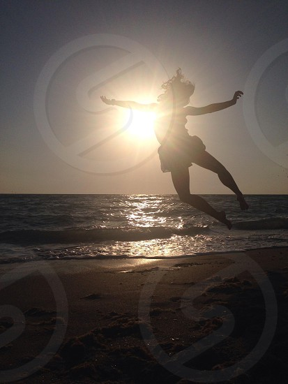 woman jumping on sea shore silhouette photo