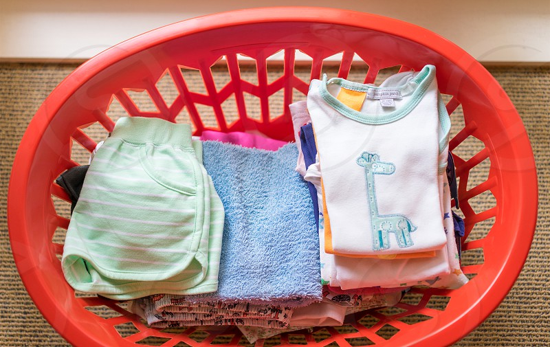 folded clothes in red plastic basket photo