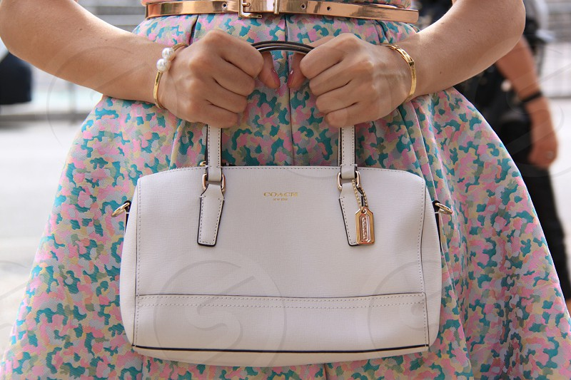 woman holding white Coach leather handbag photo