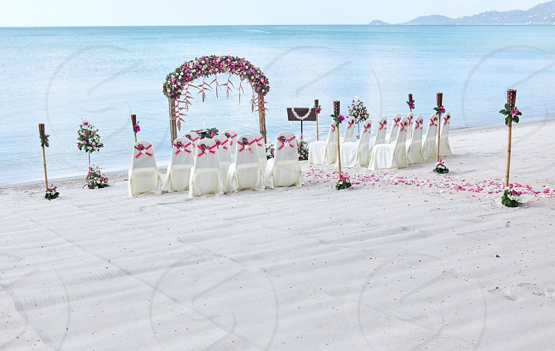 Romantic beach wedding venue settings at seaside decorate with a lot of roses petal on the aisle blue sea background photo