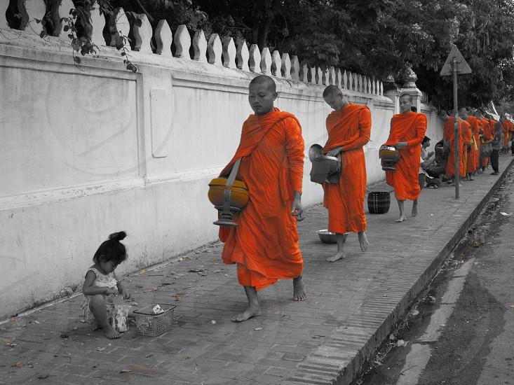 selective photo of monks walking on gray concrete sidewalk photo