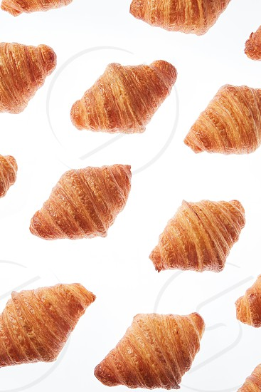 Diagonal pattern with freshly baked gourmet homemade croissants on a white background. Continental breakfast. photo