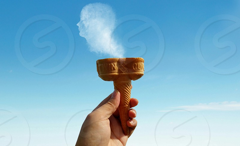 person hold brown cone with human form smoke coming out photo