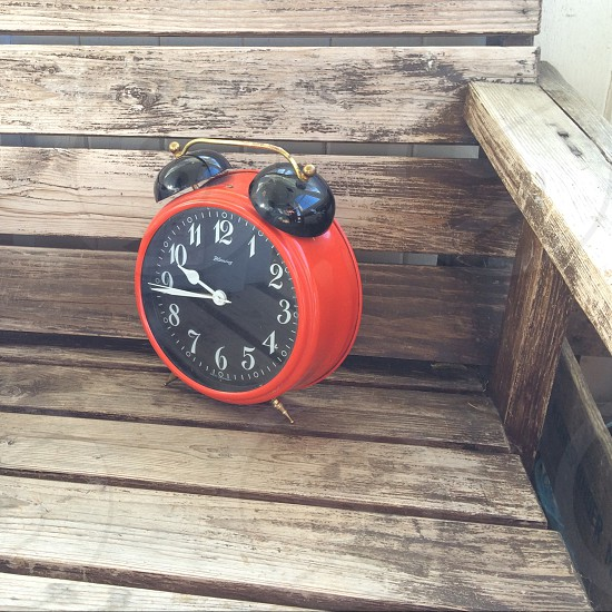 orange and black desk alarm clock on wooden chair photo