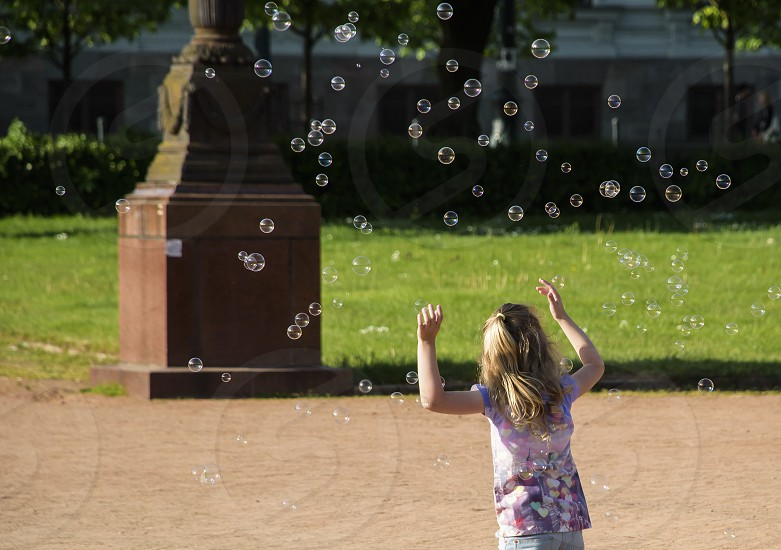 Girl chasing lots of soap bubbles in the park photo