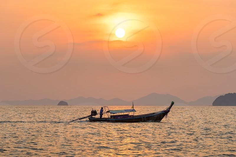 Ao Nang Krabi Province Thailand - January 14 2019: Local fisherman float on thai longtail boat in the sea water at beautiful orange sunset photo