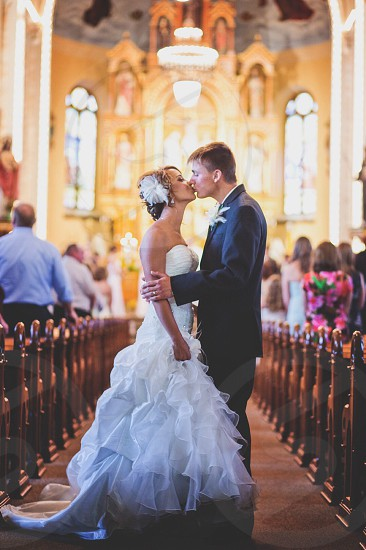 Bride and grooms first kiss in the church photo
