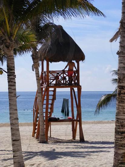 beige tall nipa hut on white sand photo