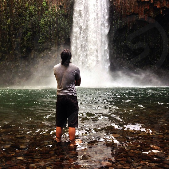 man in grey shirt standing and facing waterfalls photography photo