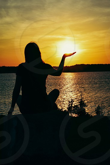 Handful of Sunlight dusk sunset girl woman female sun lake rock peaceful peace powerful power love loving relax relaxation radiant determined strong graceful shadow reflecting reflectionlight dark vivid vibrant glow golden water land hold balance horizon  photo