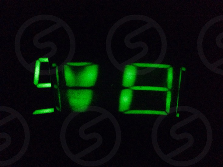 Abstract digital alarm clock seen through a glass of water photo