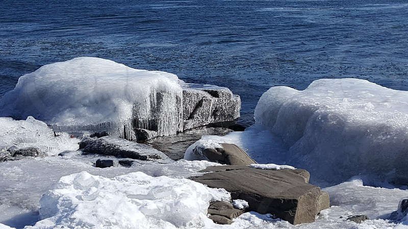 Ice icy snow rocks boulders snow covered ice covered water shoreline stones winter sparkling  photo