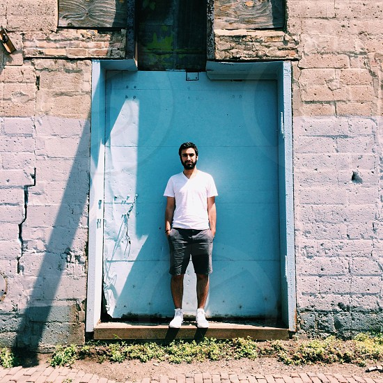 man in white tshirt standing in front of light blue metal door photo