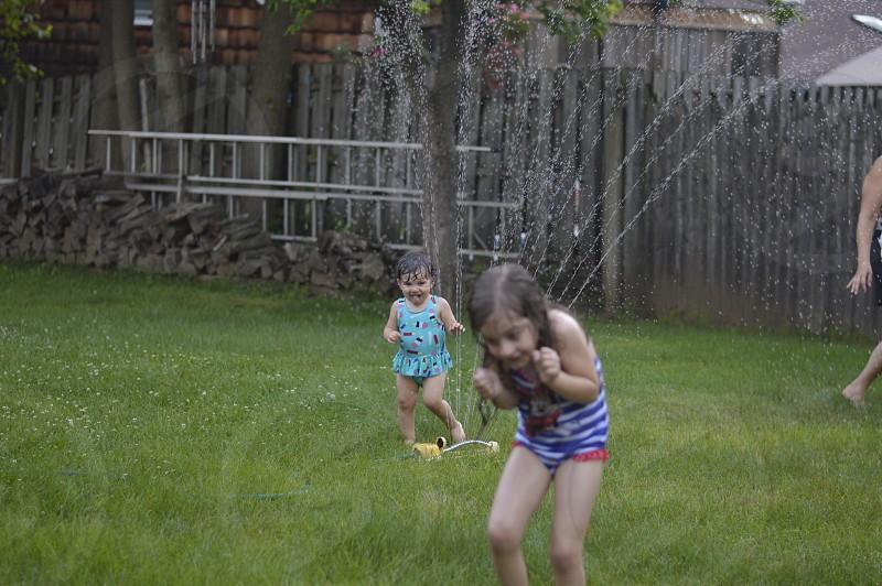 Sprinkler water hose bathing suit girls green grass wood tree yellow baby toddler fun tongue photo