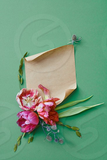 bouquet of purple flowers on a green background with a piece of kraft paper for text flat lay photo