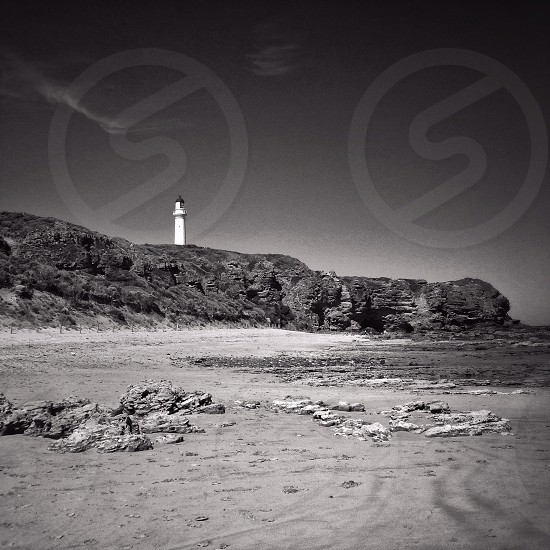 lighthouse on cliff grayscale photography  photo