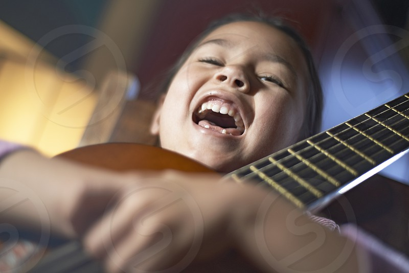 Cute young Asian girl posing with and playing her acoustic guitar photo