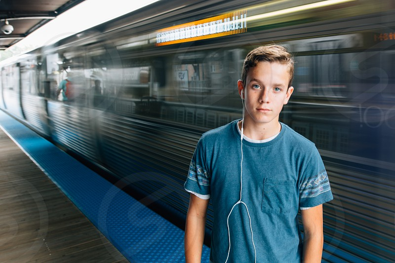 boy wearing blue crew-neck t-shirt standing near train photo