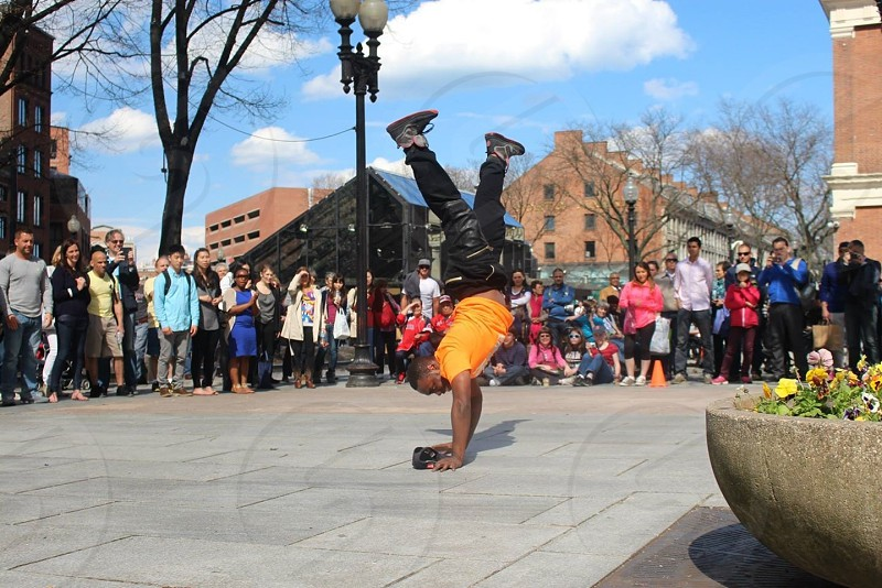 man in orange and black doing breakdancing photo